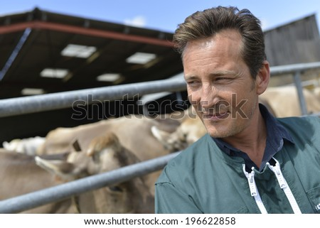 Portrait of smiling farmer standing by barn #196622858
