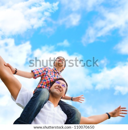 Portrait of smiling father giving his son piggyback ride outdoors against sky