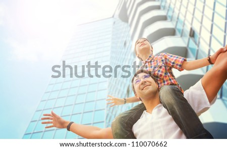 Portrait of smiling father giving his son piggyback ride outdoors against sky and modern skyscraper building