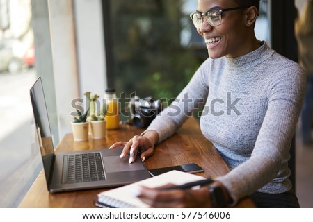Portrait of smiling female CEO communicating with employees through online video chat controlling  their work being in business trip doing remote job in coffee shop using free wireless internet