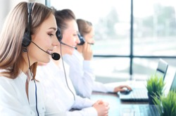 Portrait of smiling female customer service agent wearing headset with colleagues working in background at office.