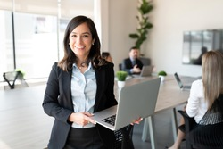 Portrait of smiling female entrepreneur holding a laptop with team in background at office conference room