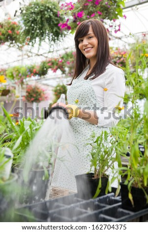 Portrait of smiling female florist watering plants in greenhouse