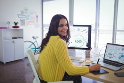 Portrait of smiling female graphic designer working in creative office