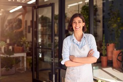 Portrait Of Smiling Female Owner Of Florists Standing In Doorway Surrounded By Plants