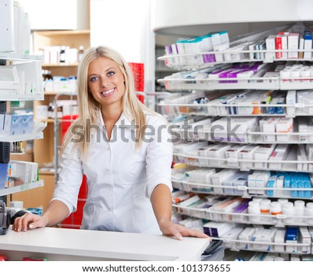Portrait of smiling female pharmacist standing at checkout counter