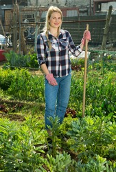Portrait of smiling female working with hoe, hoeing vegetable garden soil