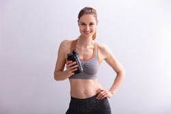 Portrait Of Smiling Fitness Woman Holding Protein Shaker Bottle Against Gray Background