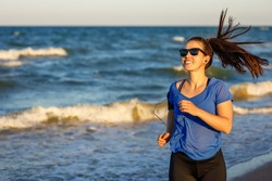 portrait of smiling fitness woman in sunglasses running and listening music in earphones with sea on the background. Healthy lifestyle girl doing exercise outdoors