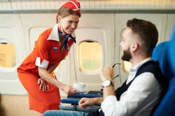 Portrait of smiling flight attendant serving coffee to young businessman in first class, copy space