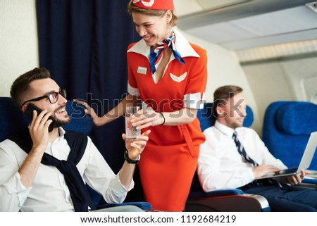 Portrait of smiling flight attendant serving glass sparkling water to handsome businessman enjoying first class trip, copy space Photo stock ©
