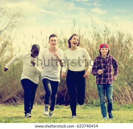 Portrait of smiling friends running on field in sunny day - Shutterstock ID 623740454