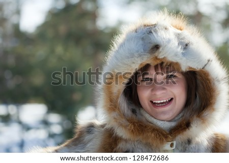 Portrait of smiling girl in fur coat at wintry park