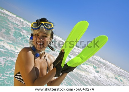 Portrait of smiling girl in swimming mask and fins on her hands against the sea and sky