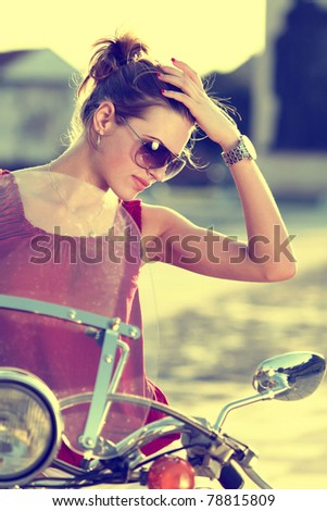 Portrait of smiling girl on scooter holding a helmet - Outdoor on street .Retro shot. Fashion art photo