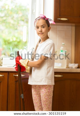 Portrait of smiling girl posing on messy kitchen with broom and scoop