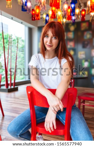 Portrait of smiling girl sitting on chair in cafe