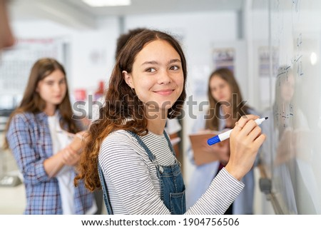 Portrait of smiling girl solving math equation on white board. College student thinking and solving arithmetic sum with classmates. Smart young woman writing on white board during class.