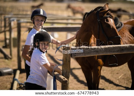 Portrait of smiling girls standing near the brown horse in the ranch