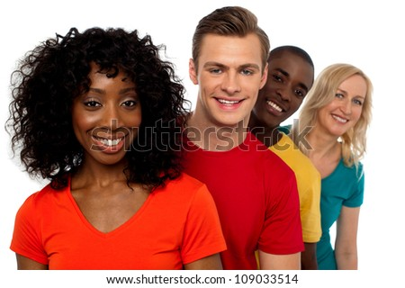 Portrait of smiling group of friends standing behind one another facing camera