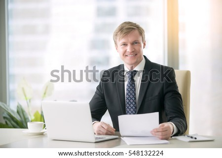 Portrait of smiling handsome businessman working with documents, laptop at the desk in modern office, screening potential business deals by analyzing market strategies, resume reviewing, organized