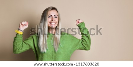 Portrait Of Smiling happy blonde woman With The Fists Up celebrates her success, poses against beige Background #1317603620
