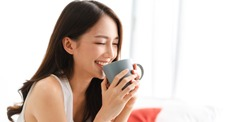 Portrait of smiling happy cheerful beautiful pretty asian woman relaxing drinking and looking at cup of hot coffee or tea.Girl felling enjoy having breakfast in holiday morning vacation on bed at home