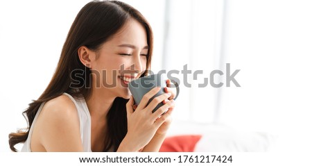 Portrait of smiling happy cheerful beautiful pretty asian woman relaxing drinking and looking at cup of hot coffee or tea.Girl felling enjoy having breakfast in holiday morning vacation on bed at home Foto stock ©