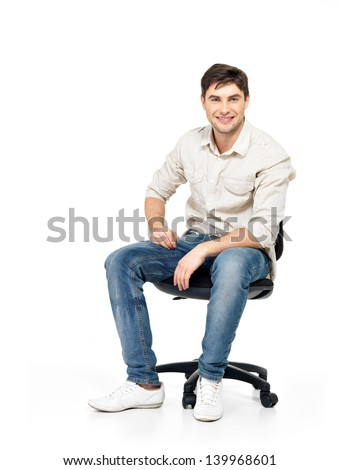 Portrait of smiling happy man sits on the office chair isolated on white.