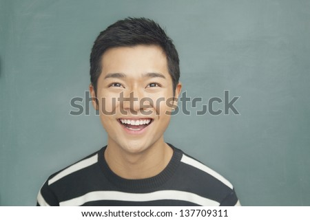 Portrait of smiling, happy young man in front of blackboard