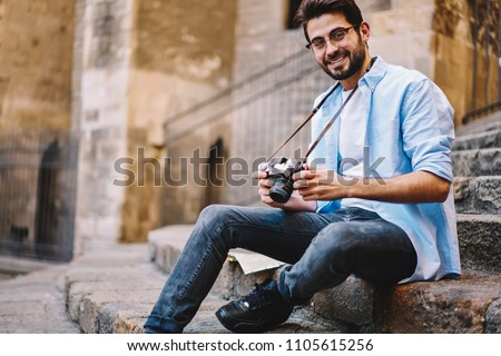 Portrait of smiling hipster guy with vintage camera sitting on stairs resting during touristic tour, positive male photographer in spectacles looking at camera checking equipment for making pictures