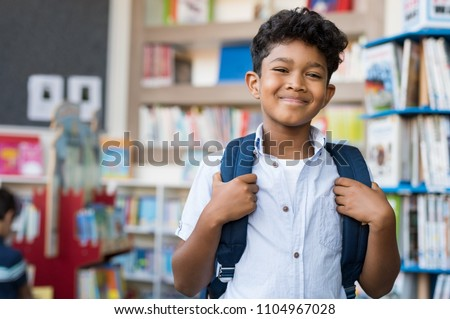 Portrait of smiling hispanic boy looking at camera. Young elementary schoolboy carrying backpack and standing in library at school. Cheerful middle eastern child standing with library background.