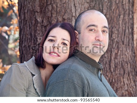 Portrait of smiling husband and wife couple hugging and looking at the camera.