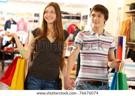 Portrait of smiling husband and wife looking at some goods in the mall