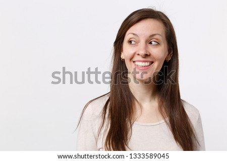 Portrait of smiling joyful pretty young woman in light clothes standing and looking aside isolated on white wall background in studio. People sincere emotions lifestyle concept. Mock up copy space #1333589045