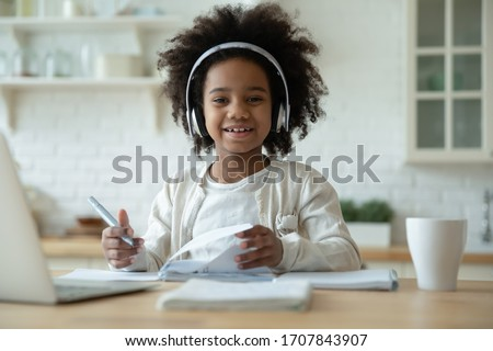 Portrait of smiling little biracial girl in headphones do homework study online in kitchen, happy small African American child in earphones have online web class or lesson using laptop at home