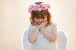 Portrait of smiling little curly blond Angel girl with wreath made of roses. Child with angelic character. Toddler girl wearing angel costume (white dress and feather wings). Consept of innocent child