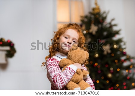 Stock Photo portrait of smiling little girl hugging teddy bear at home