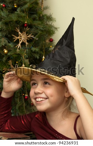 Portrait of smiling little girl in witch hat at christmas tree