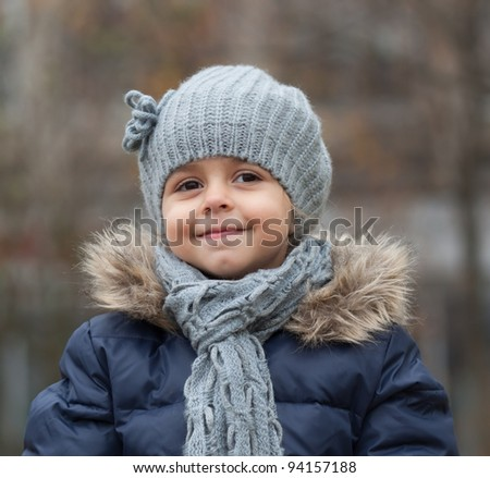 Portrait of smiling little girl with knit hat and scarf.