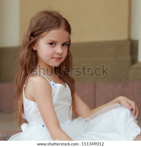 Portrait of smiling little girl with long hair in a beautiful dress is sitting on the steps