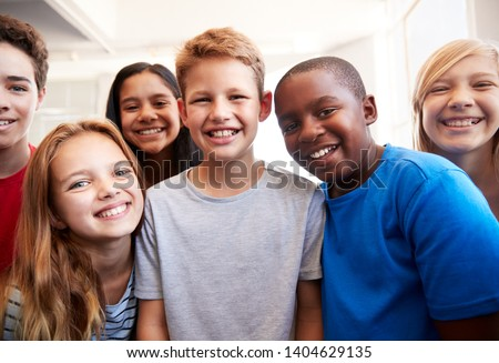 Portrait Of Smiling Male And Female Students In Grade School Classroom