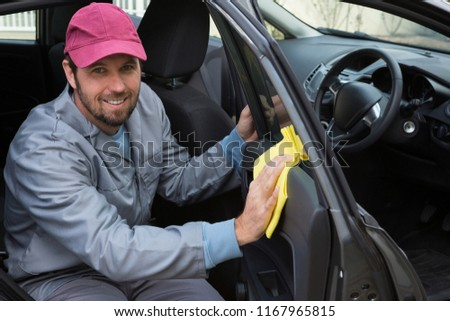 Portrait of smiling male auto service staff cleaning car door