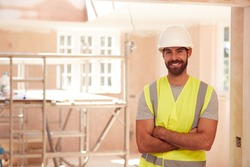 Portrait Of Smiling Male Builder Wearing Hard Hat Working In New Build Property