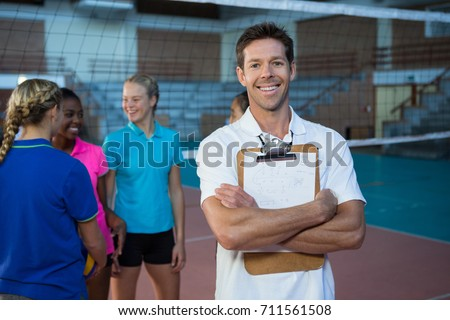 Portrait of smiling male coach standing in the volleyball court