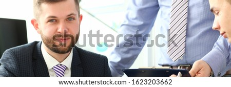 Portrait of smiling male holding paper tablet with important document that determine future of colossal corporation and discussing agreement with colleagues. Company meeting concept
