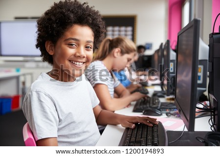Portrait Of Smiling Male Pupil Sitting In Line Of High School Students Working at Screens In Computer Class Stock photo ©