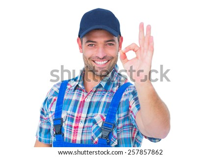 Portrait of smiling male repairman gesturing okay on white background