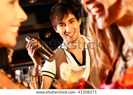 Portrait of smiling male with bottle looking at camera in the bar