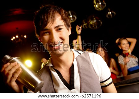 Portrait of smiling male with bottle looking at on background of dancers
